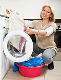 Woman using washing machine at home laundry Stock Photo
