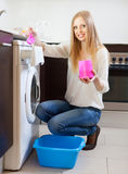 Woman using washing machine with laundry detergent Stock Image