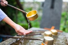 Woman using the water bamboo ladle for purification Royalty Free Stock Photo