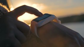 Woman using wearable smart watch. Woman using wearable smartwatch computer device on deck of cruise ship at sunset. Sunset light, sun lens flares, golden hour stock footage