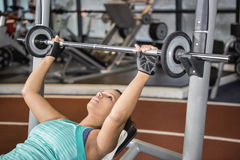 Woman using weight machines Stock Images