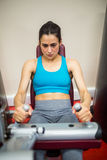Woman using weights machine Royalty Free Stock Photography