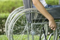 Woman using a wheelchair in a park. Close up Royalty Free Stock Photo