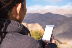 A woman using white mobile phone with blank screen while standing in front of mountain and blue sky. Mockup image of a woman using white mobile phone with blank Royalty Free Stock Images