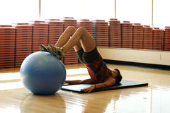 Woman using work out ball to stretch. In gym Stock Image
