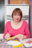 Woman with utility bills. Sad mature woman with utility bills at her home stock photo