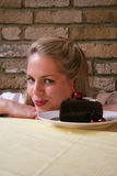 Woman v cheery chocolate cake - Temptation 2. Image of a blonde woman with a sneaky naughty expression thinking about eating a chocolate cake, conceptual dieting stock photography
