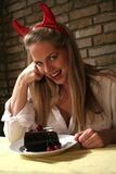 Woman v Chocolate Cake Devils Temptation. Image of a blond woman with devil horns being tempted by a cherry chocolate cake, conceptual temptation royalty free stock image