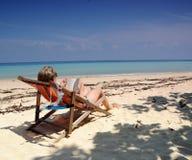 Woman on Vacation. Woman in bikini reading on beach Royalty Free Stock Photos