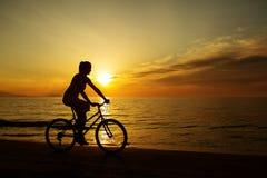 Woman on vacation biking at beach Stock Photography