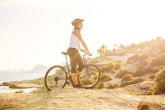 Woman on vacation biking at beach Stock Photos