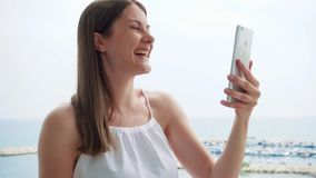 Woman on vacation having video chat with friend on balcony via mobile messenger app in slow motion. Smiling young woman in white dress using mobile on balcony stock video