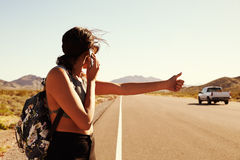 Woman On Vacation Hitchhiking Along Road Using Mobile Phone Royalty Free Stock Images