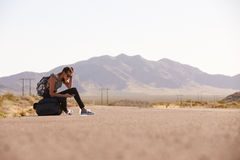 Woman On Vacation Hitchhiking Along Road Using Mobile Phone Royalty Free Stock Photos