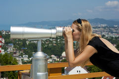 Woman on vacation looking through binoculars Stock Images