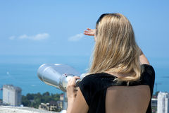 Woman on vacation looking through binoculars Royalty Free Stock Image