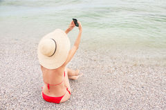Woman on vacation is making self portrait by smart phone. Royalty Free Stock Photography