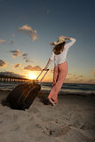 Woman on vacation at the ocean during a sunrise. Woman on vacation looking at the ocean during a sunrise with a pier in background Stock Photo