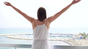 Woman on vacation raise arms up on terrace with sea view. Female outstretching hands in slow motion. Young woman raising arms up on balcony with sea view in stock video footage