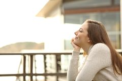 Woman on vacation relaxing at hotel. Side view portrait of a happy woman on vacation relaxing at hotel terrace on the beach Stock Photos