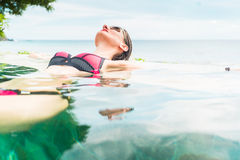 Woman in vacation relaxing swimming in pool Royalty Free Stock Photography