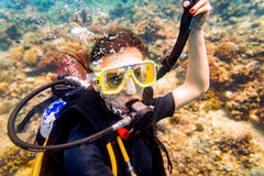 Woman in vacation scuba diving to tropical coral reef. Woman in vacation scuba diving down to tropical coral reef royalty free stock image