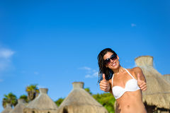 Woman on vacation at tropical resort beach with thumbs up Stock Photos