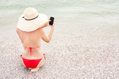 Woman on vacation is using smart phone (mobile) on the beach. Royalty Free Stock Images