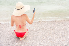 Woman on vacation is using smart phone (mobile). Stock Image
