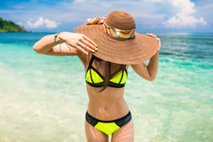 Woman on vacation wearing beach hat bathing in ocean royalty free stock photos