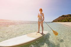 Woman at vacation. Wide angle view of young woman enjoying stand up paddleboarding in beautiful turquoise lagoon at tropical island, active vacation concept, sun Royalty Free Stock Photo