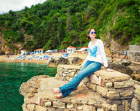Woman on vacations. Young woman sitting on the stones near the beach Royalty Free Stock Image