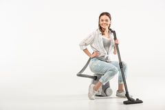 Woman with vacuum cleaner. Attractive young woman sitting on vacuum cleaner and smiling at camera royalty free stock image
