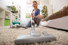 Woman with vacuum cleaner cleaning carpet stock photos