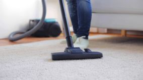 Woman with vacuum cleaner cleaning carpet at home. People, housework and housekeeping concept - woman with vacuum cleaner cleaning carpet at home stock video