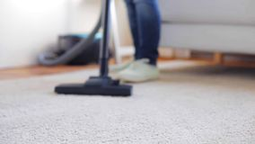 Woman with vacuum cleaner cleaning carpet at home stock footage