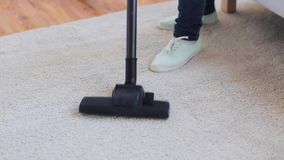 Woman with vacuum cleaner cleaning carpet at home. People, housework and housekeeping concept - woman with vacuum cleaner cleaning carpet at home stock footage
