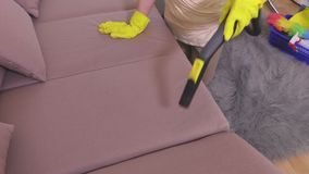 Woman with vacuum cleaner cleaning on sofa unavailable places. In room stock video