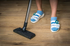 Woman with vacuum cleaner cleaning wooden laminate floor Stock Photos