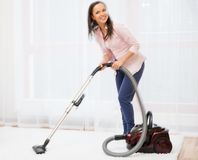 Woman vacuum cleaning carpet Stock Photo