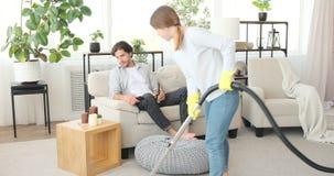 Woman vacuuming carpet quarrels husband drinking beer and watching tv
