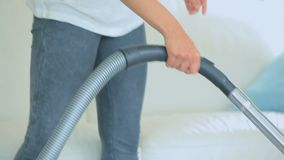 Woman vacuuming the carpet. Video of woman vacuuming the white carpet with hoover stock footage