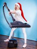 Angry girl in santa helper hat with vacuum cleaner Royalty Free Stock Image