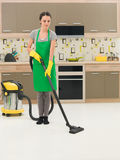 Woman vacuuming kitchen floor Royalty Free Stock Image