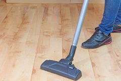 Woman is vacuuming laminate floor Royalty Free Stock Images
