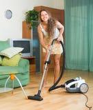 Woman vacuuming living room Royalty Free Stock Photography