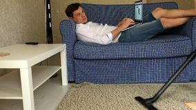 Woman vacuuming, man listening to music on laptop, resting on sofa. Fhd stock video footage