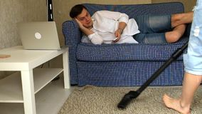 Woman vacuuming, man with phone resting on the couch. Fhd stock video footage