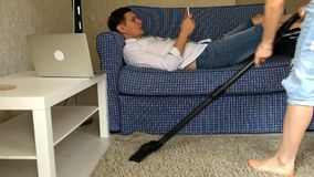 Woman vacuuming, man with phone resting on the couch. Fhd stock footage