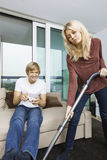 Woman vacuuming while man play video game in living room at home Stock Images